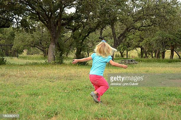 Toddler Girl Spinning Outdoors