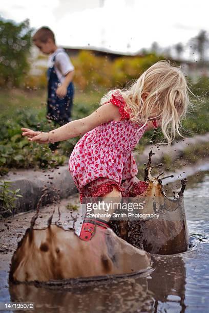 Toddler girl splashing in mud
