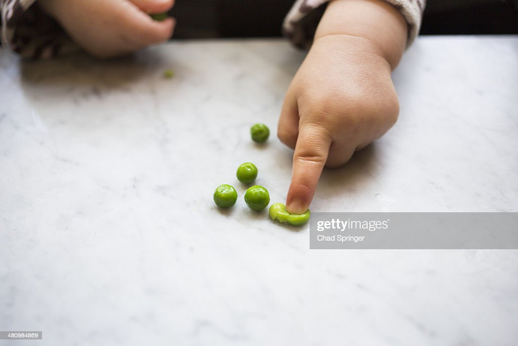 Toddler girl squashing pea : Stock Photo