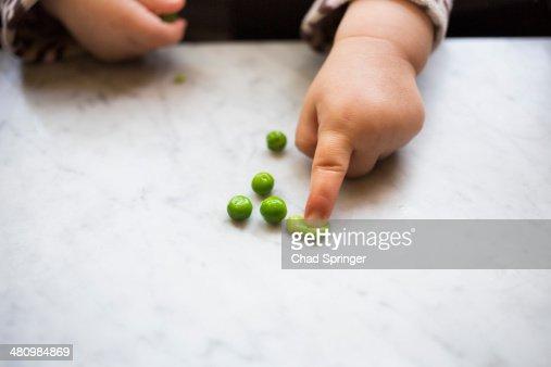 Toddler girl squashing pea