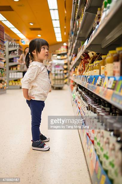 Toddler girl standing in front of a grocery shelf