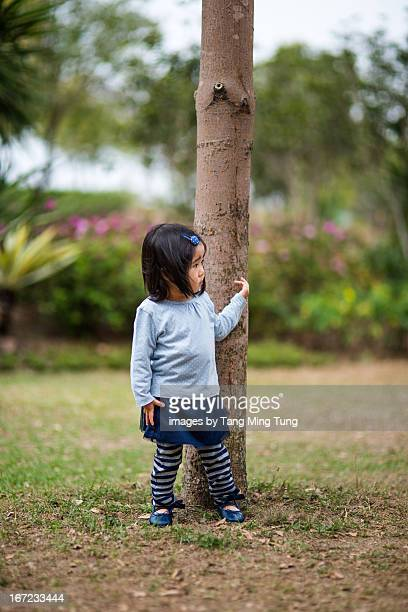 Toddler girl standing next to a tree looking away