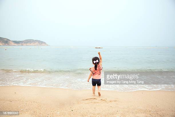Toddler girl standing on beach waving at the sea