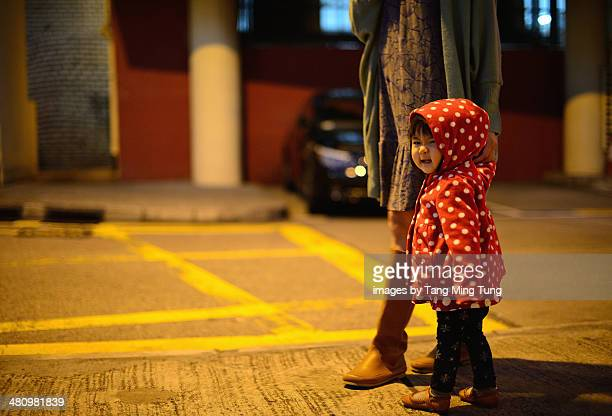 Toddler girl strolling in the street with mom