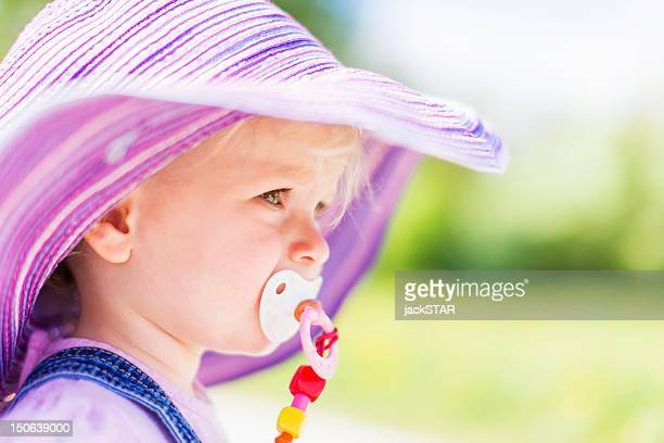 Toddler girl sucking pacifier outdoors