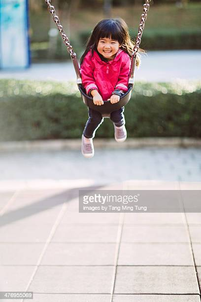 Toddler girl swinging on a swing joyfully