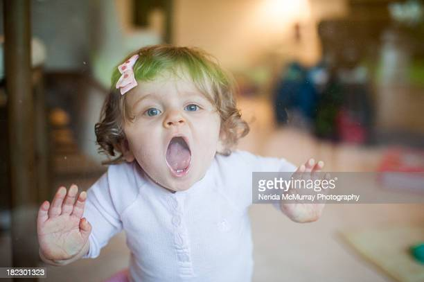 Toddler girl up against glass door