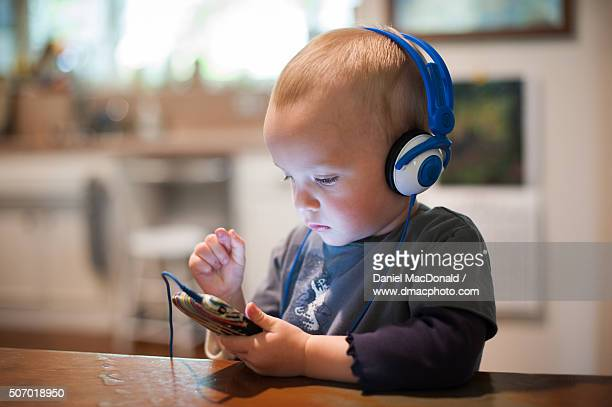 Toddler girl using a smartphone while listening to music on headphones