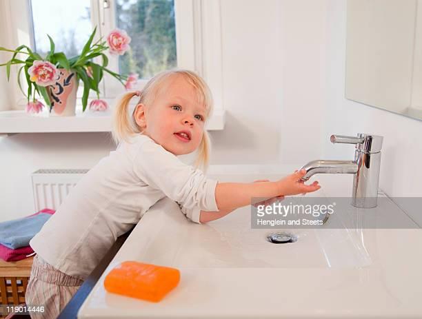 Toddler girl washing her hands