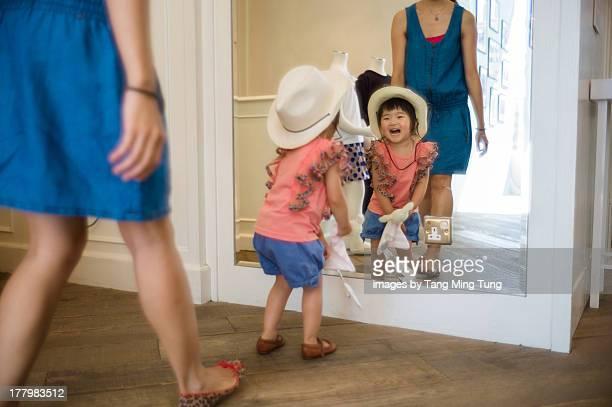 Toddler girl wearing cowboy hat looking at mirror
