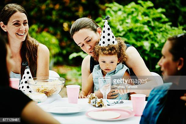 Toddler girl wearing party hat sitting with aunt