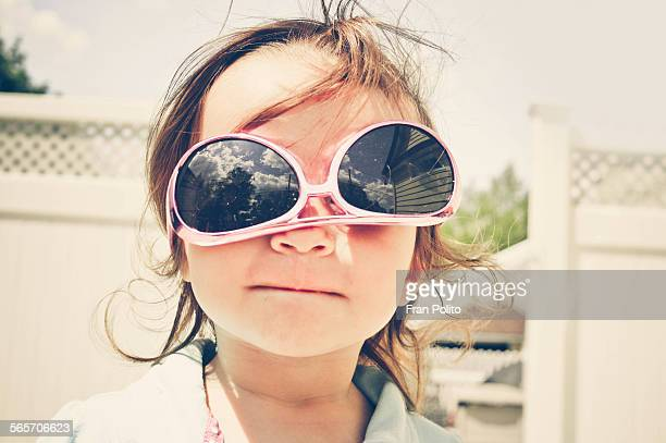 A toddler girl wearing sunglasses upside down
