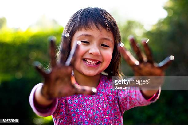 Toddler girl with muddy hands