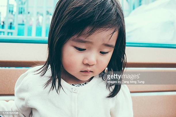 Toddler girl with sorrowful face sitting on bench