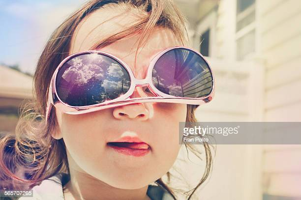 Toddler girl with sunglasses being silly.