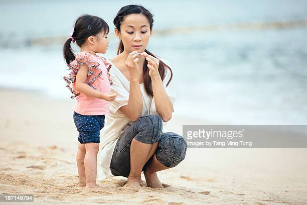 Toddler girl & young mom playing on the beach