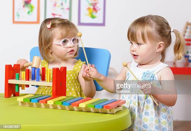 Toddler Girls Interacting  And Enjoying Music In A Nursery Setting