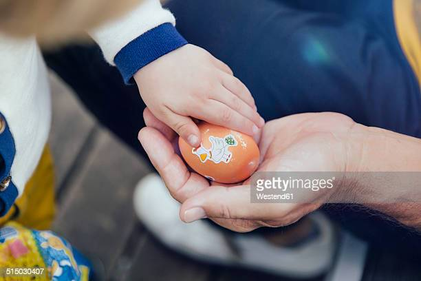 Toddler giving his grandfather an Easter egg, close-up
