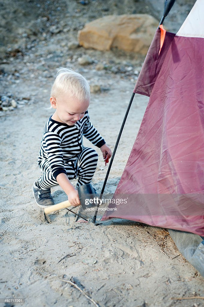 Toddler hammering tent peg with mallet