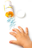 toddler hand taking parent prescription pills from above on white background