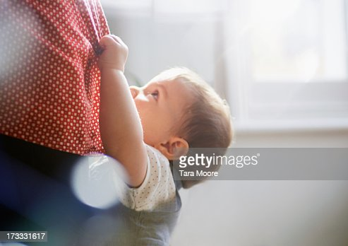 toddler hanging on to mother's dress
