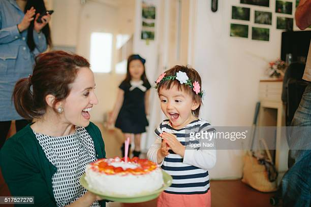 Toddler happily excited by blowing out candles on birthday cake