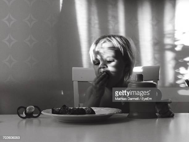 Toddler Having Food While Sitting At Table