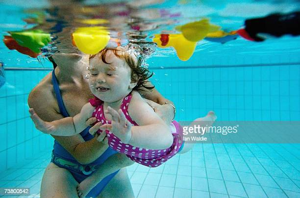 A toddler held by her mother swims underwater in a search for toys during a swimming class for babies at Lane Cove pool March 16 2007 in Sydney...