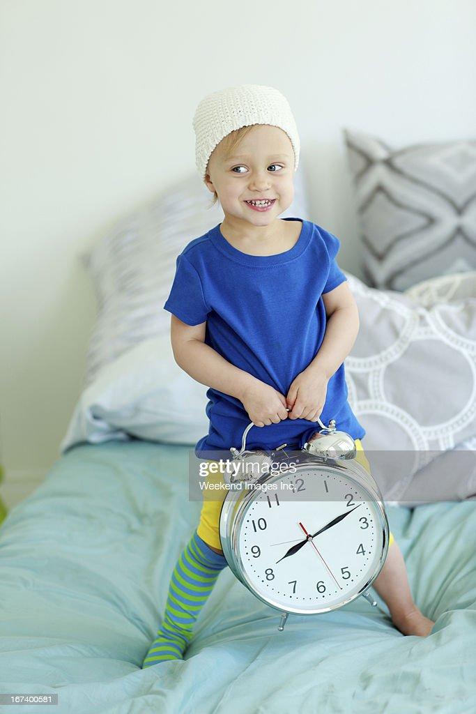 Toddler holding  alarm clock : Stock Photo