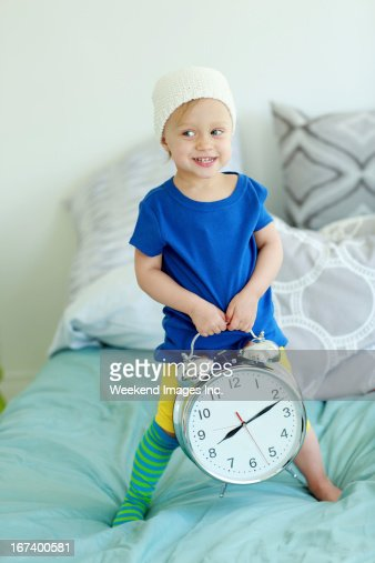 Toddler holding  alarm clock : Stock Photo