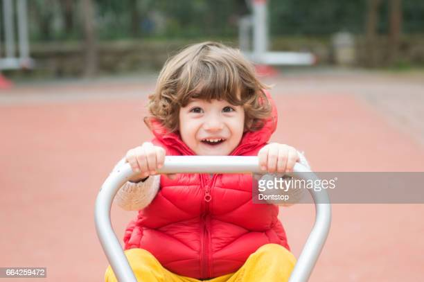 Toddler holding handle of seesaw
