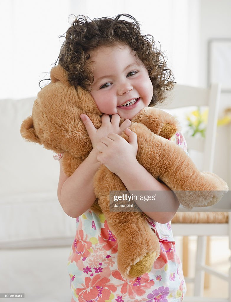 Toddler hugging teddy bear, smiling : Stock Photo