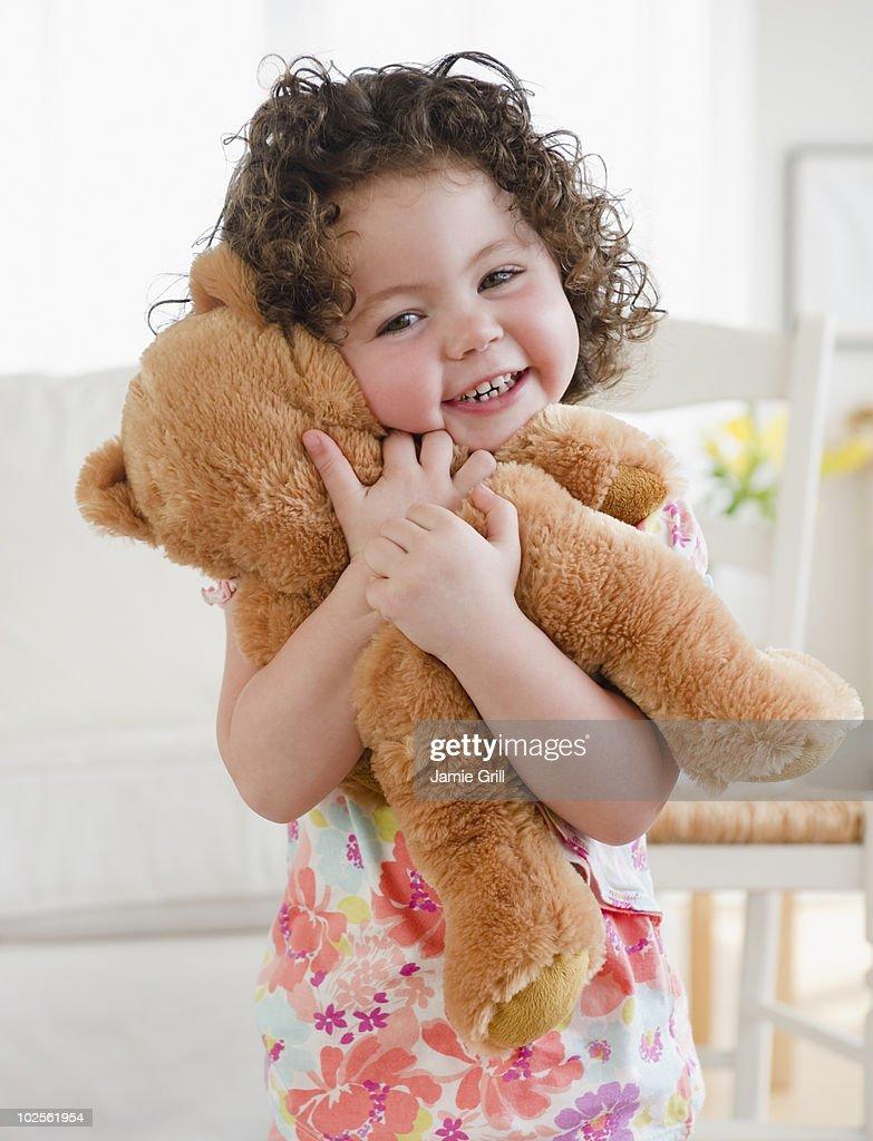 Toddler hugging teddy bear, smiling