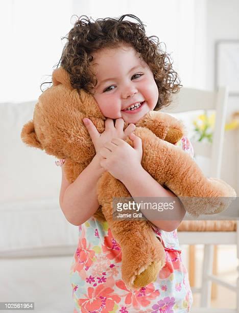 Toddler hugging teddy bear, smiling