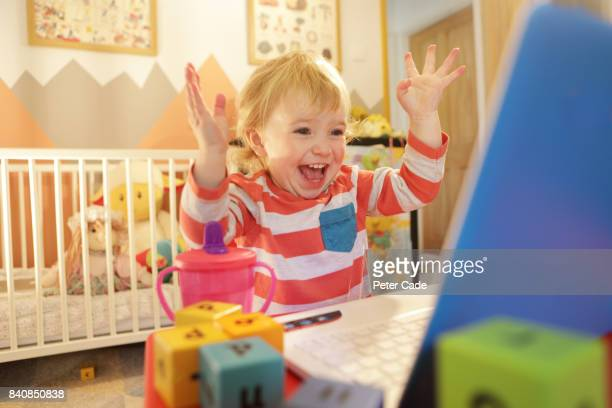 Toddler in bedroom working on laptop, looking happy