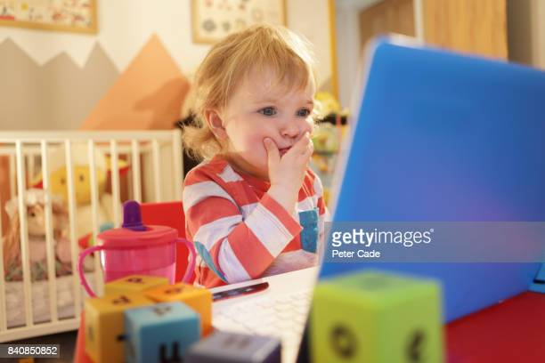 Toddler in bedroom working on laptop, looking worried