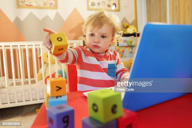 Toddler in bedroom working on laptop