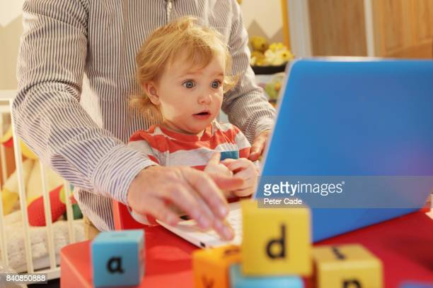 Toddler in bedroom working on laptop with father