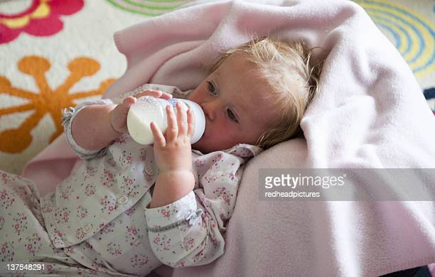 Toddler in blanket drinking from bottle