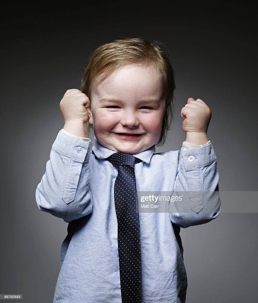 Toddler in business attire, giving a cheer : Stock Photo