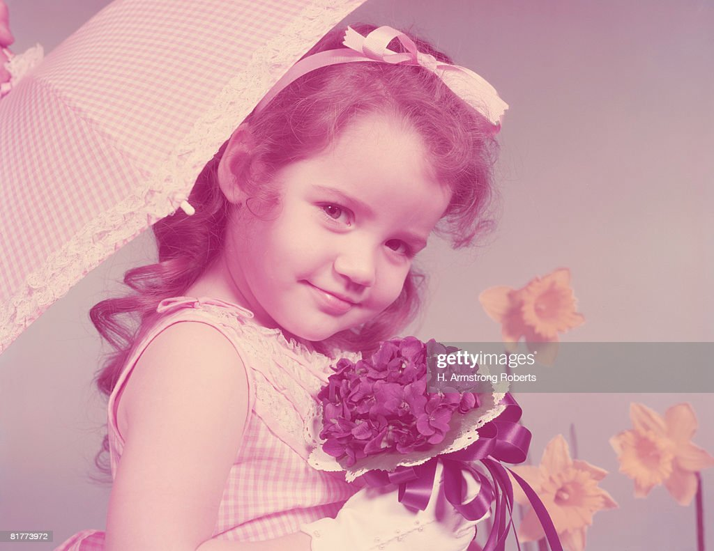 Toddler in gingham dress, holding parasol and violet posey. (Photo by H. Armstrong Roberts/Retrofile/Getty Images) : Stock Photo
