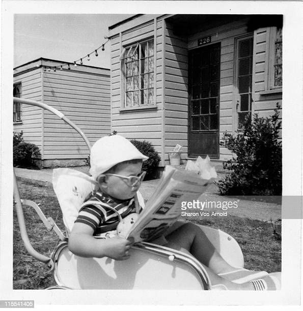 Toddler in his buggy, reading newspaper