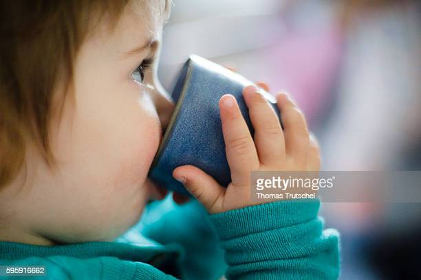 A toddler is drinking from a cup on August 11 2016 in Berlin Germany