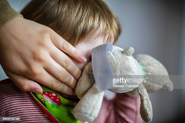 A toddler is hiding his face behind a stuffed toy while her mother runs her hand over his face on August 12 2016 in Berlin Germany