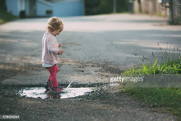 Toddler jumping in a puddle