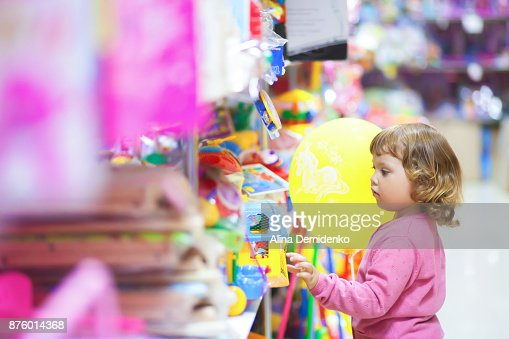 Toddler kid shopper at the toy shop. : Stock Photo