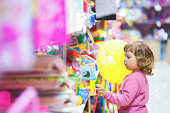 Toddler kid at the mall, choosing toys, lifestyle.