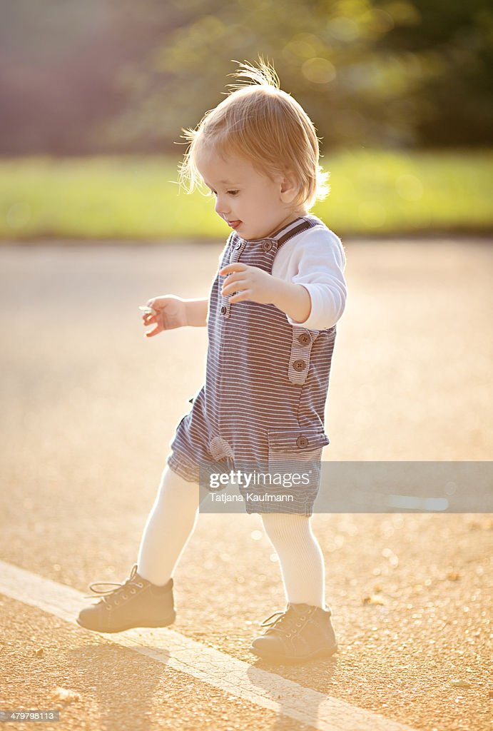 Toddler learning to Walk first time on Street