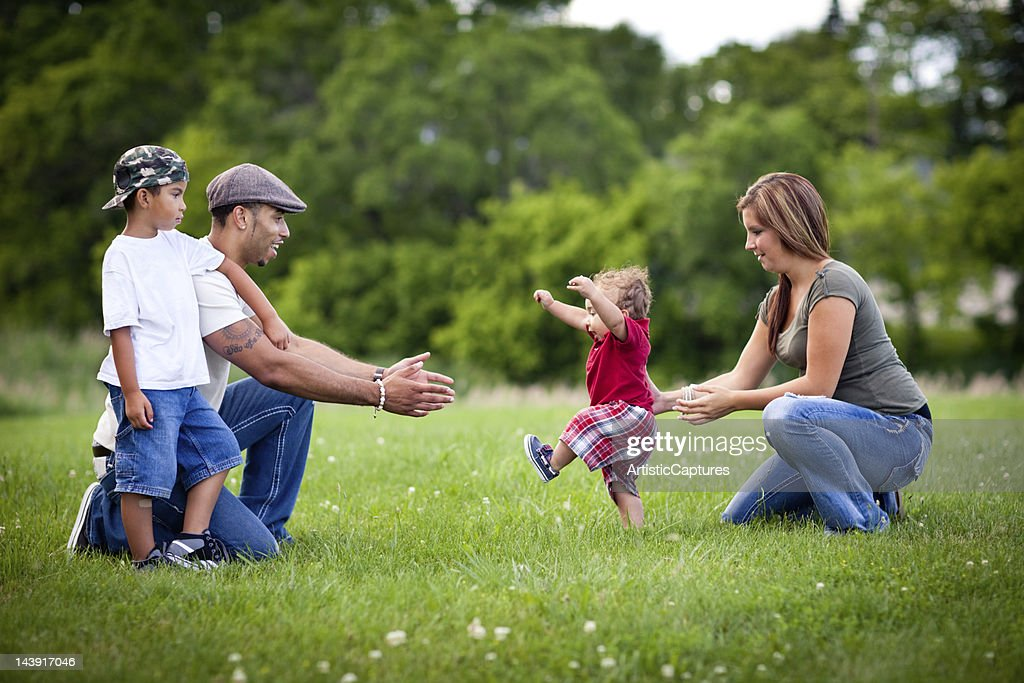 Toddler Learning to Walk with Happy Family Outside