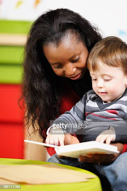 Toddler/ Little Boy Enjoying Storytime With His Carer At Nursery